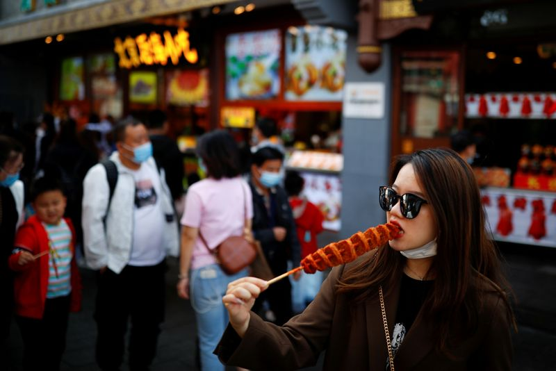 © Reuters. FILE PHOTO: A woman eats as people walk in the tourist area surrounding Houhai Lake during Chinese National Day holidays in Beijing
