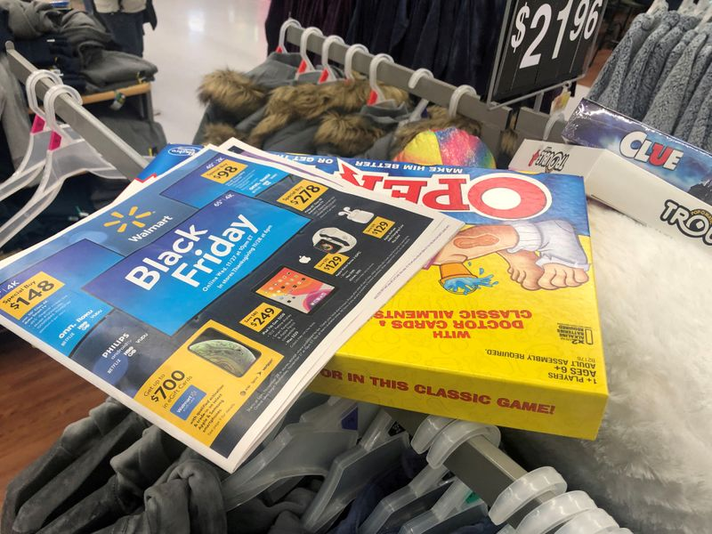 © Reuters. FILE PHOTO: Black Friday ads lay on top of clothes during a sales event on Thanksgiving day at Walmart in Westbury, New York