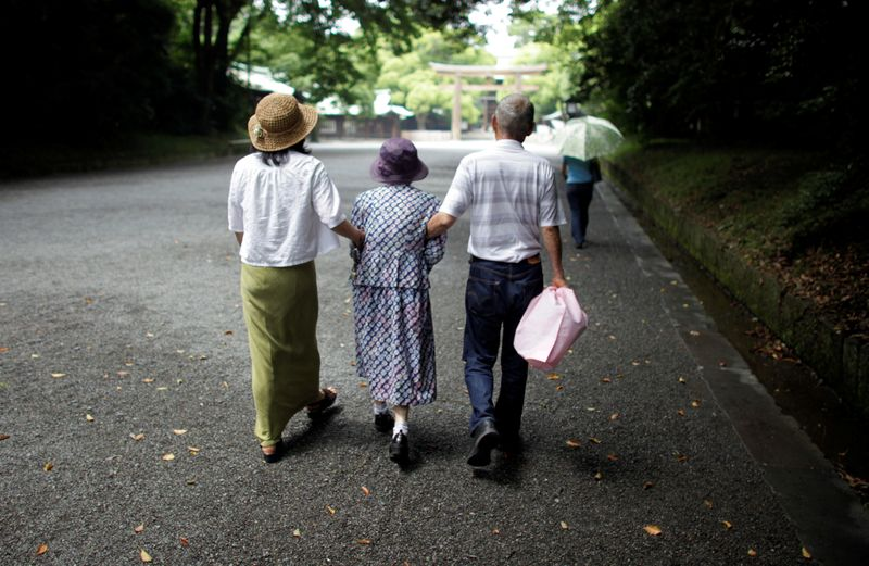 © Reuters. FILE PHOTO: An elderly woman is led to a temple in Tokyo in this July 17, 2009 file photo