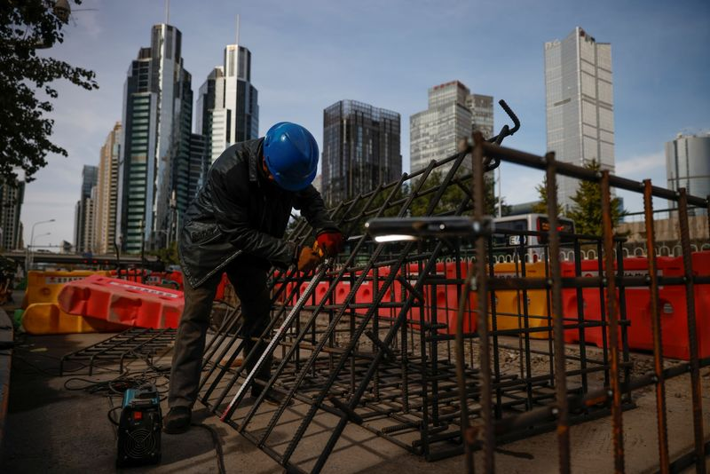 © Reuters. Workers prepares an iron grid for welding at a construction site in the Central Business District (CBD) following an outbreak of the coronavirus disease (COVID-19) in Beijing