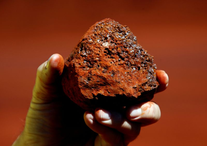© Reuters. FILE PHOTO: A miner holds a lump of iron ore at a mine located in the Pilbara region of Western Australia