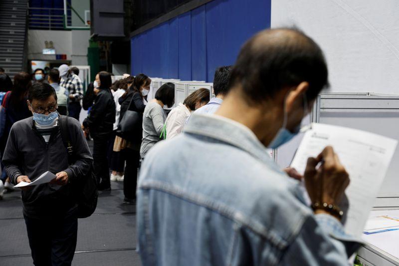 © Reuters. Job seekers wearing face masks fill in forms at the Wan Chai Job Fair, following the coronavirus disease (COVID-19) outbreak, in Hong Kong