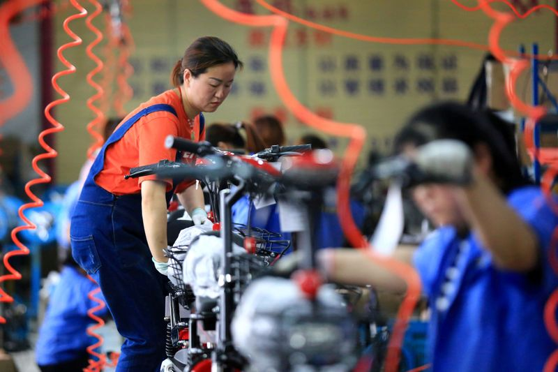 © Reuters. FILE PHOTO: Woman work on manufacturing electric bicycles at a factory in Huaian, Jiangsu