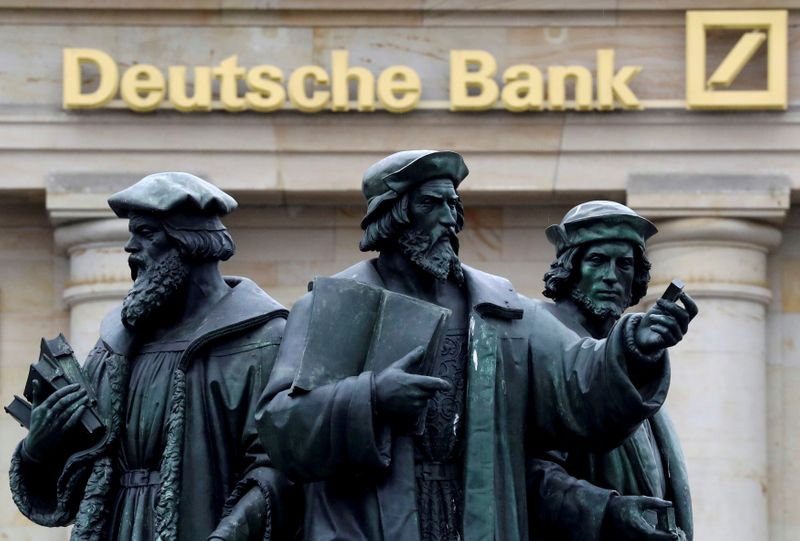 © Reuters. FILE PHOTO: A statue is pictured next to the logo of Germany's Deutsche Bank in Frankfurt
