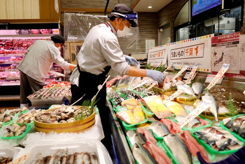 © Reuters. FILE PHOTO: A staff wearing a face shield sells fish at Japan's supermarket group Aeon's shopping mall as the mall reopens amid the coronavirus disease (COVID-19) outbreak in Chiba