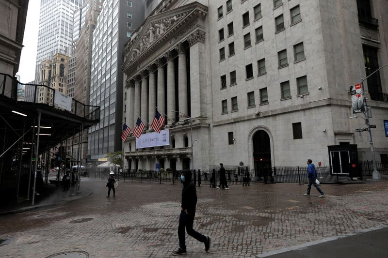 © Reuters. FILE PHOTO: People wearing protective face masks walk outside New York Stock Exchange in New York