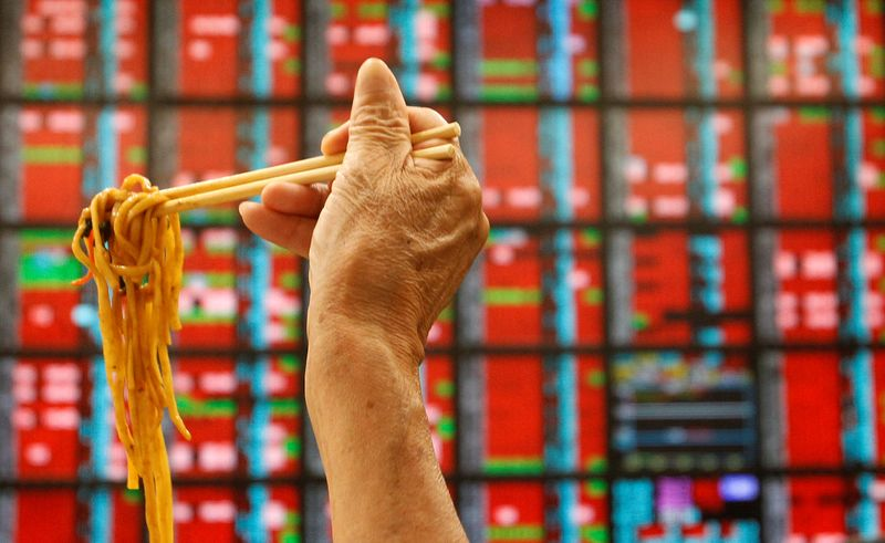 © Reuters.  FILE PHOTO: A man eats a noodle lunch while watching the stock market price inside a brokerage company in Taipei