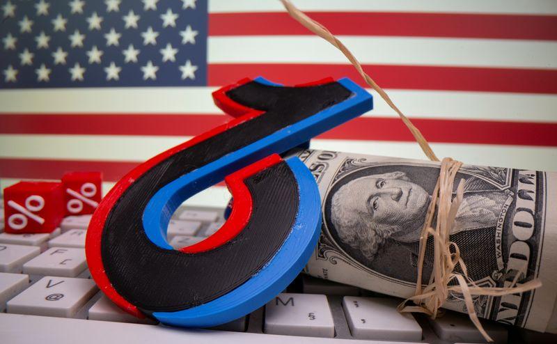 © Reuters. IMAGEN DE ARCHIVO. El logo impreso en 3D de Tik Tok junto a billetes de dólares en un teclado se ven delante de una bandera de Estados Unidos en esta ilustración