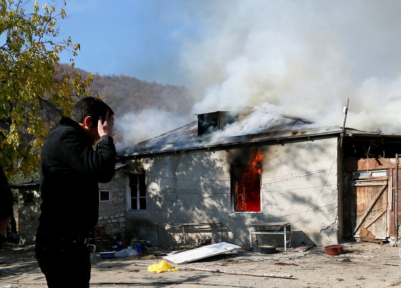 © Reuters. A man reacts as he stands near a house set on fire by departing Ethnic Armenians in the village of Cherektar, in the region of Nagorno-Karabakh