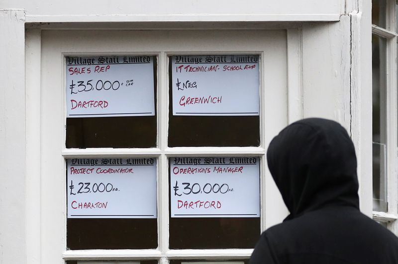 © Reuters. FILE PHOTO: A person looks at adverts in the window of a job agency in London