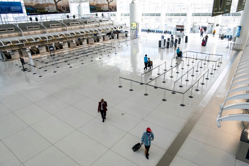 © Reuters. FILE PHOTO: People walk around the terminal at the John F. Kennedy International Airport in New York