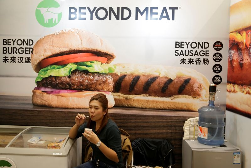 © Reuters. A woman sits next to a poster at the booth of plant-based food company Beyond Meat at VeggieWorld fair in Beijing