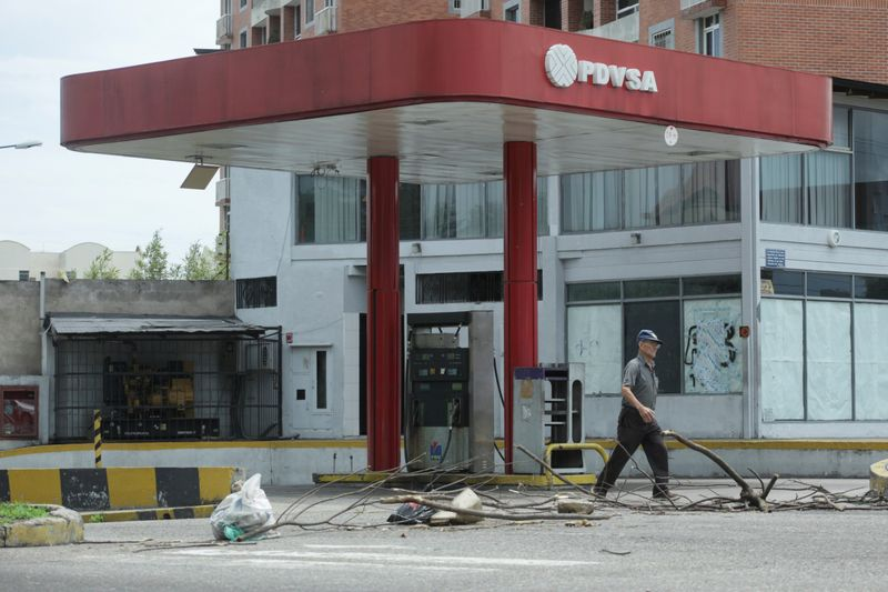 © Reuters. FILE PHOTO: A man walks past a closed gas station of the state oil company PDVSA in San Cristobal