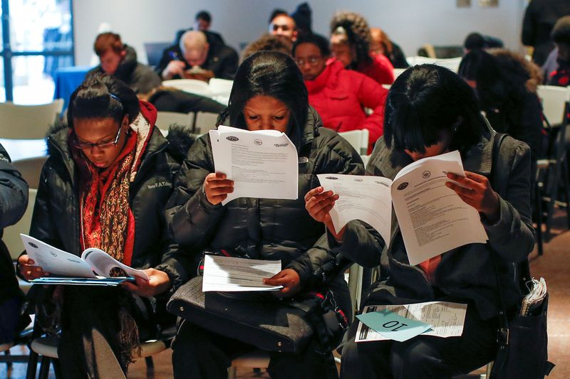 © Reuters. FILE PHOTO: People fill out application forms before a screening session for seasonal jobs at Coney Island in the Brooklyn borough of New York