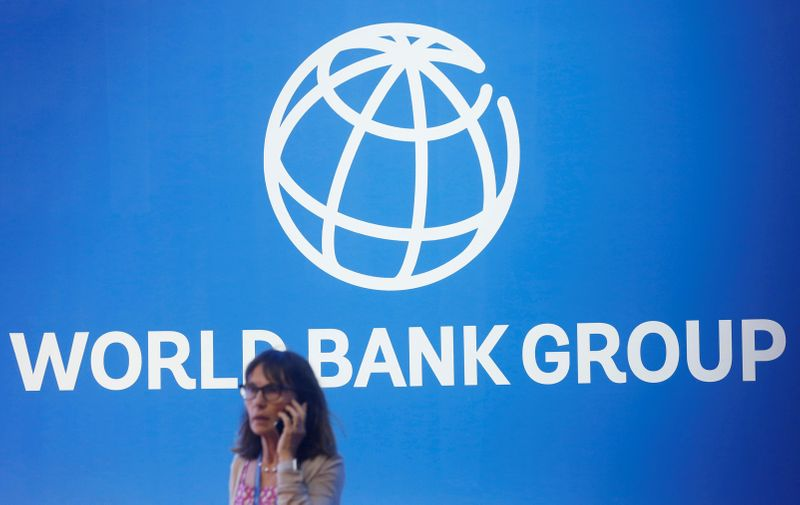 © Reuters. FILE PHOTO: A participant stands near a logo of World Bank at the International Monetary Fund - World Bank Annual Meeting 2018 in Nusa Dua