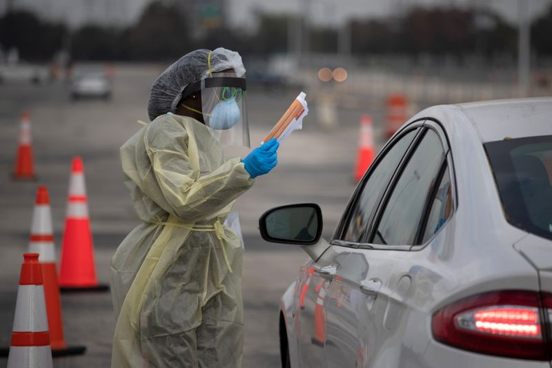 © Reuters. A healthcare worker holds a coronavirus disease (COVID-19) informational pamphlet for a resident at a drive-thru testing location in Houston