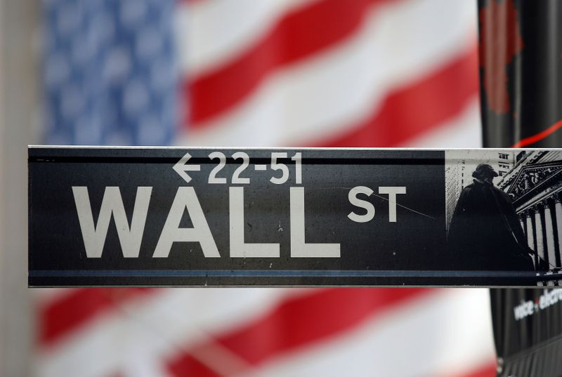 © Reuters. FILE PHOTO: A sign for Wall Street is seen with a giant American flag in the background across from the New York Stock Exchange