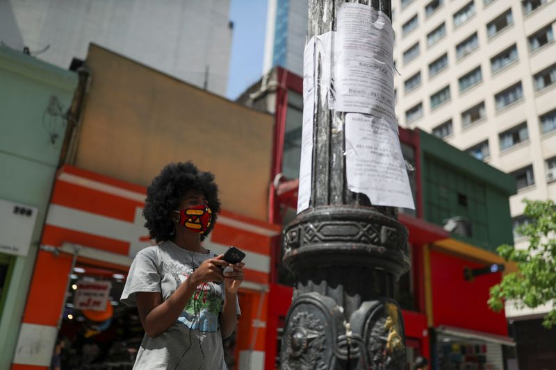 © Reuters. FILE PHOTO: A woman looks at job listings posted on a light pole in downtown Sao Paulo