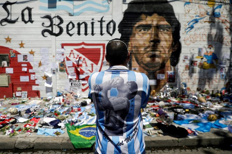 © Reuters. FILE PHOTO: People mourn the death of soccer legend Diego Armando Maradona, in Buenos Aires