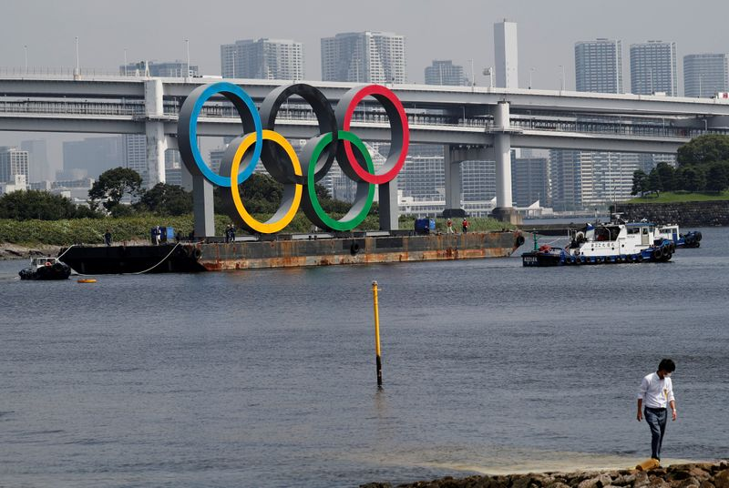 © Reuters. FILE PHOTO: Boats tow the giant Olympic rings, which are being temporarily removed for maintenance, at the waterfront area at Odaiba Marine Park in Tokyo
