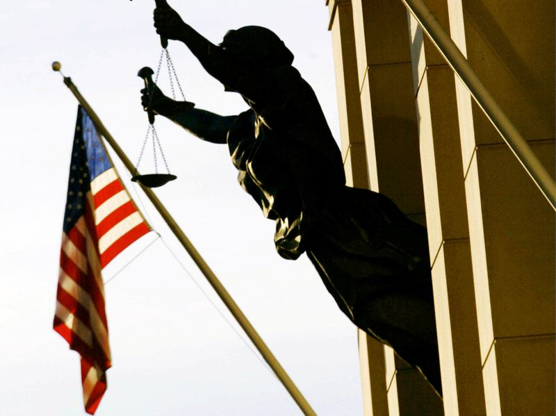 © Reuters. FILE PHOTO: THE AMERICAN FLAG FLIES NEXT TO A STATUE OF THE SCALES OF JUSTICE.