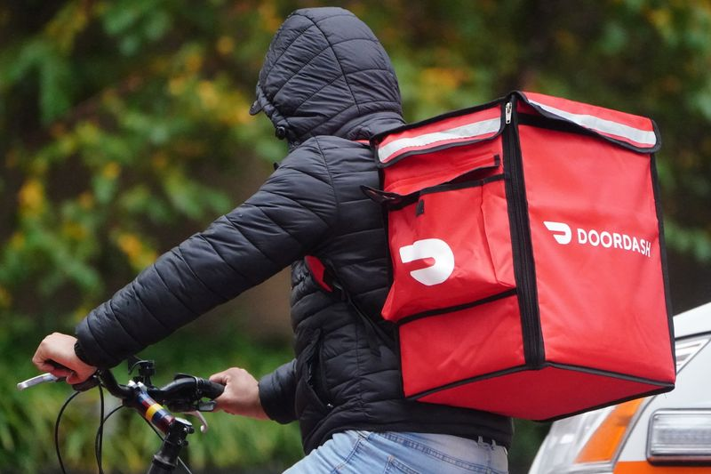 © Reuters. FILE PHOTO: A delivery person for Doordash rides his bike in the rain during the coronavirus disease (COVID-19) pandemic in the Manhattan borough of New York City
