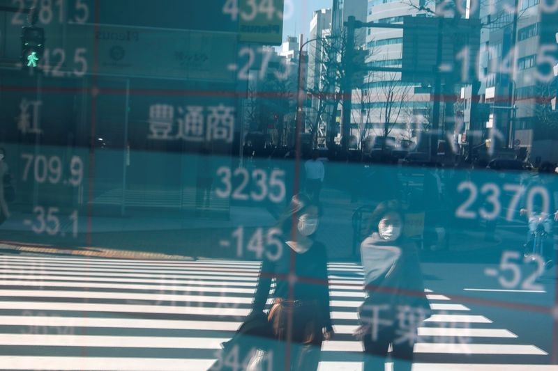 © Reuters. People wearing protective face masks, following an outbreak of the coronavirus, are reflected on a screen showing Nikkei index, outside a brokerage in Tokyo