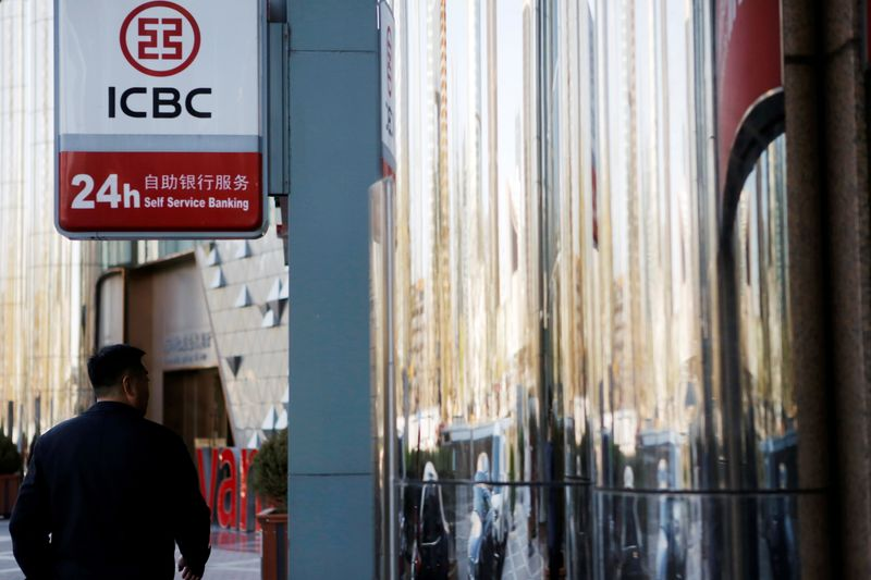 © Reuters. FILE PHOTO: Man walks past a branch of Industrial and Commercial Bank of China (ICBC) in Beijing