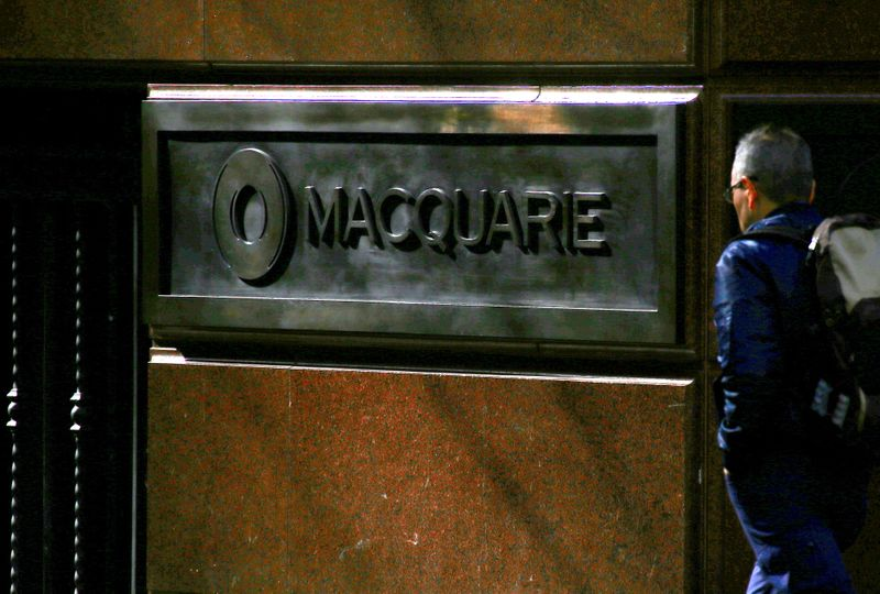 © Reuters. FILE PHOTO: A pedestrian walks past the logo of Australia's Macquarie Group at the firm's headquarters in central Sydney