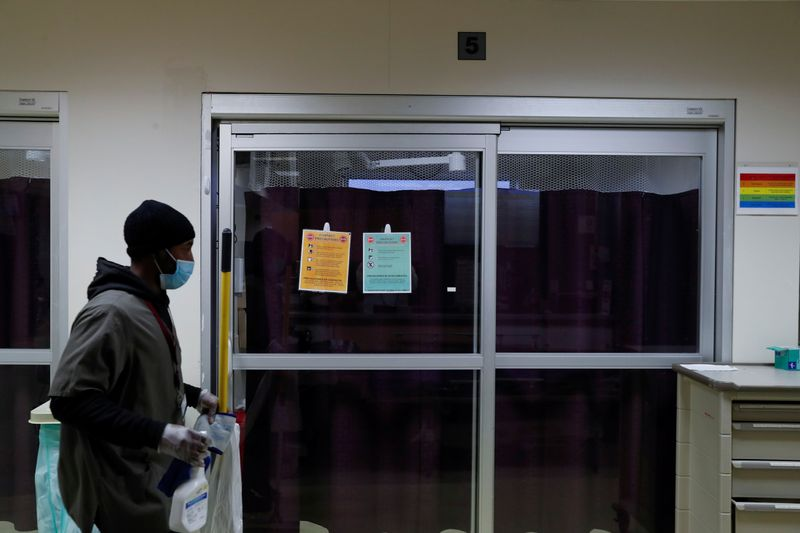 © Reuters. FILE PHOTO:  A housekeeper walks by the isolation room of a coronavirus disease (COVID-19) positive patient inside the emergency room bed at Roseland Community Hospital on the South Side of Chicago, Illinois