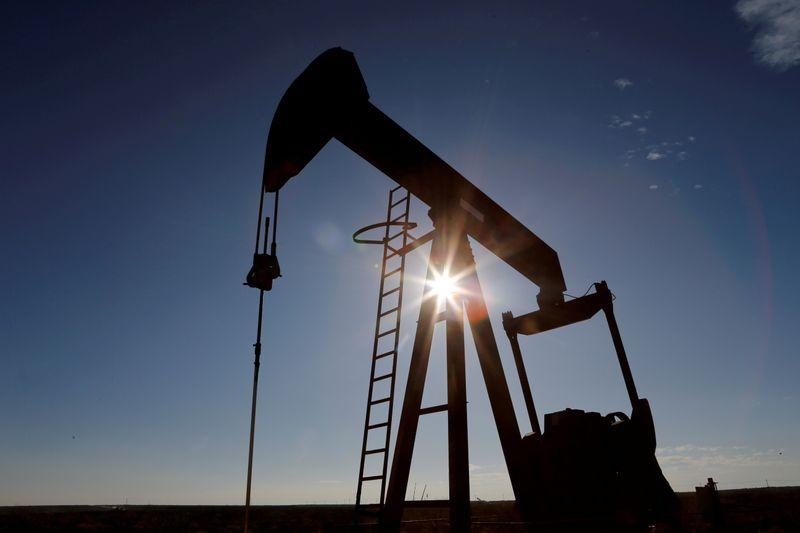 © Reuters. Raggi del sole filtrano da una pompa per l'estrazione di petrolio greggio nel bacino del Permiano