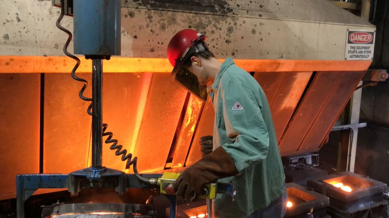 © Reuters. FILE PHOTO: A worker pours hot metal at the Kirsh Foundry in Beaver Dam