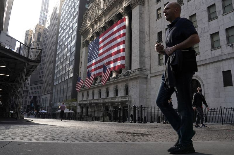© Reuters. FILE PHOTO: People walk past the New York Stock Exchange