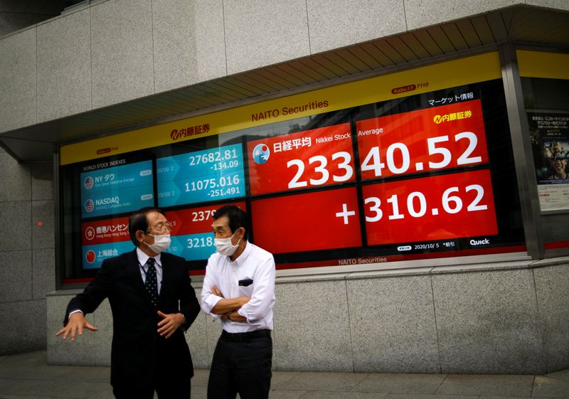 © Reuters. Men wearing protective face masks chat in front of a screen displaying Nikkei share average and world stock indexes, amid the coronavirus disease (COVID-19) outbreak, in Tokyo