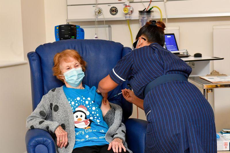 © Reuters. Margaret Keenan, una nonna di 90 anni dell'Irlanda del Nord, è diventata oggi la prima persona al mondo a ricevere il vaccino sviluppato da Pfizer contro il Covid-19 presso lo University Hospital, somministrato dall'infermiera May Parsons, a Co