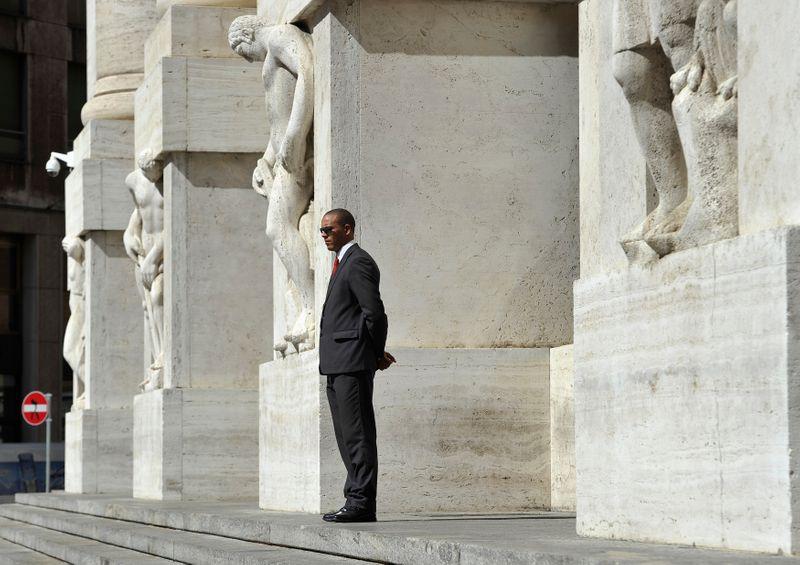© Reuters. Un uomo fermo davanti all'ingresso della Borsa di Milano