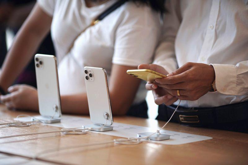 © Reuters. Diversi clienti provano i nuovi iPhone 11, iPhone 11 Pro, e iPhone 11 Pro Max presso un Apple Store a Hong Kong