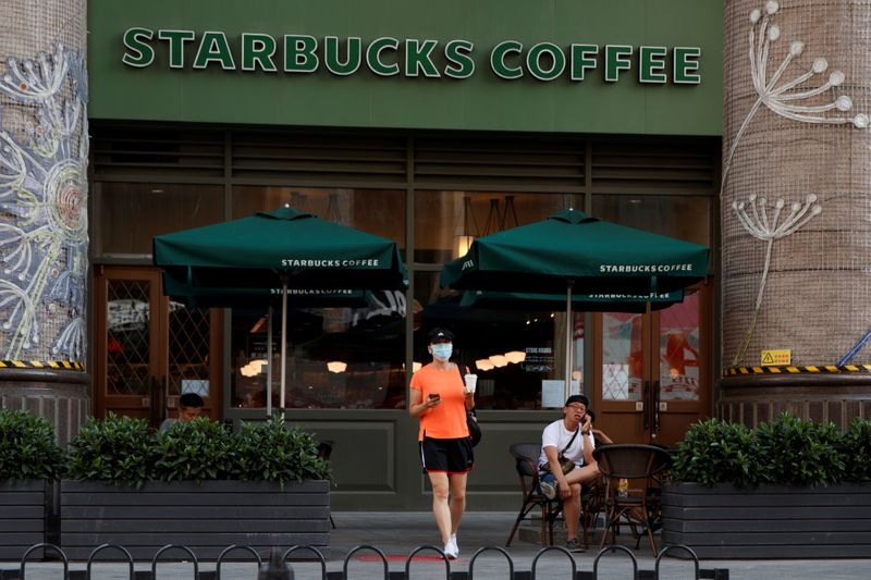 © Reuters. A woman leaves a cafe of Starbucks Coffee in Beijing