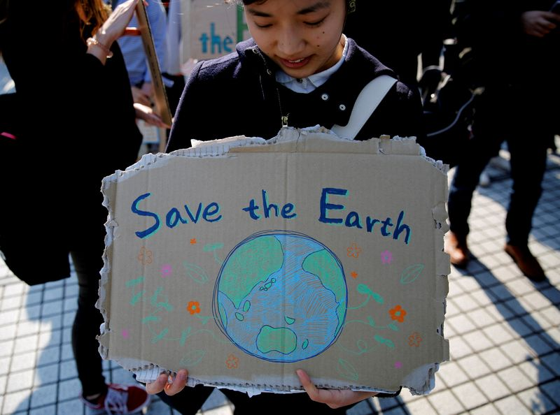 © Reuters. FILE PHOTO: A school student holds a sign as she takes part in the global students strike for action on climate change in Tokyo