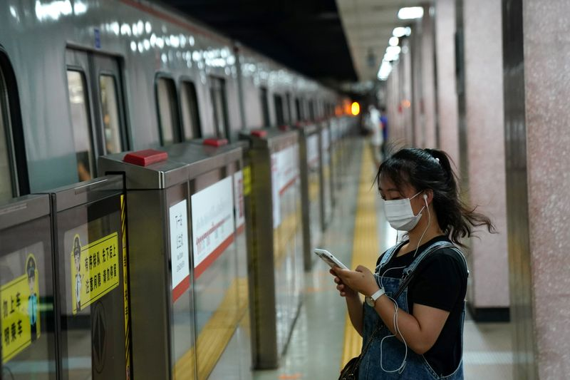 © Reuters. Woman wearing a face mask following  coronavirus disease (COVID-19) outbreak looks at her smartphone while waiting for a subway in Beijing