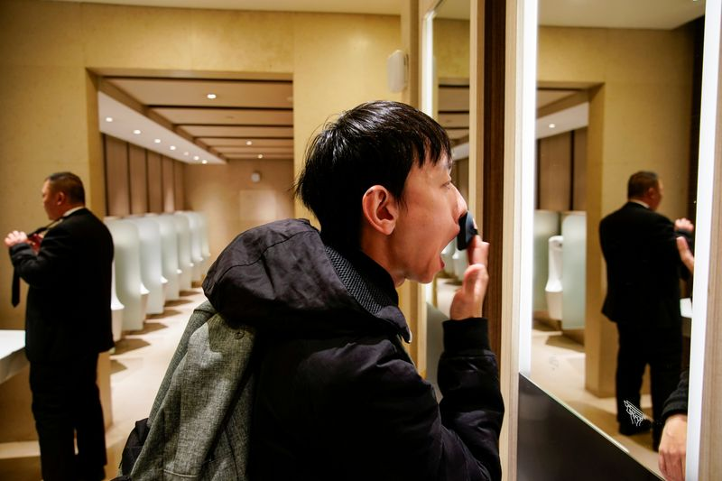 © Reuters. Liu Yuxuan, 22, a student, puts on his make-up at a restroom in a shopping mall in Shanghai