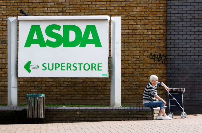 © Reuters. FILE PHOTO: A shopper sits by an Asda superstore sign in south London