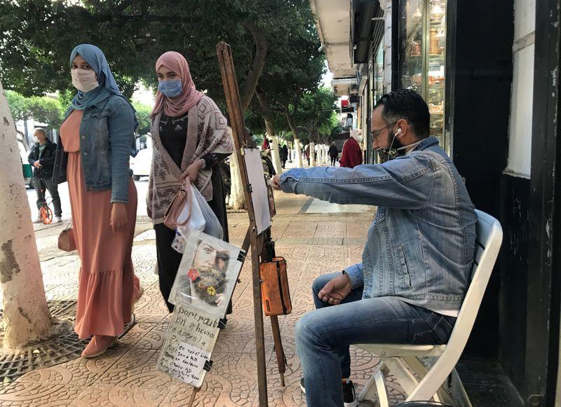 © Reuters. A man draws as women walk on a street in Algiers