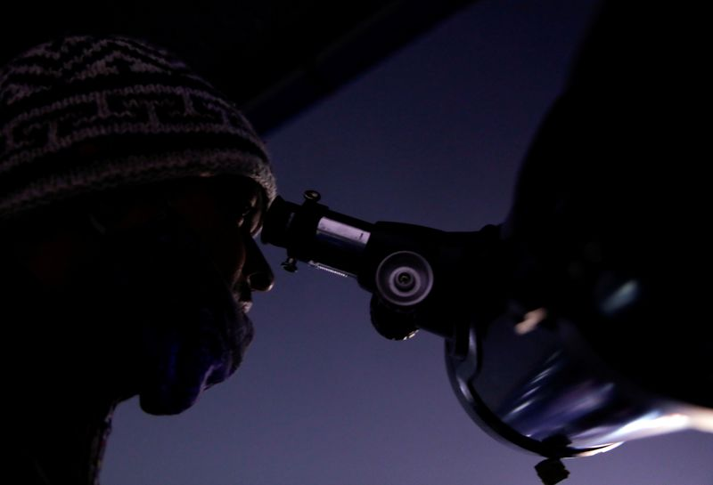© Reuters. FILE PHOTO: Man observes the closest visible conjunction of Jupiter and Saturn, through a telescope in Kathmandu