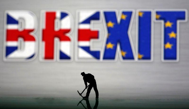 © Reuters. Una piccola figura giocattolo di fronte a un logo della Brexit