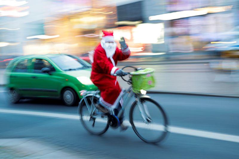 © Reuters. FILE PHOTO: 'Santa Claus' rides a bike on city street