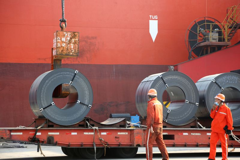 © Reuters. FILE PHOTO:  Workers load steel products for export to a cargo ship at a port in Lianyungang