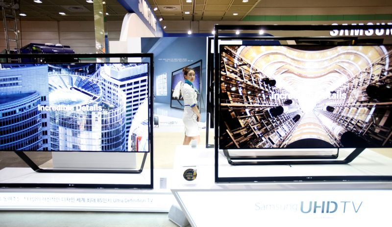 © Reuters. FILE PHOTO: A model stands between Samsung Electronics' Ultra HD LCD televisions during World IT show 2013 at the Coex convention centre in Seoul