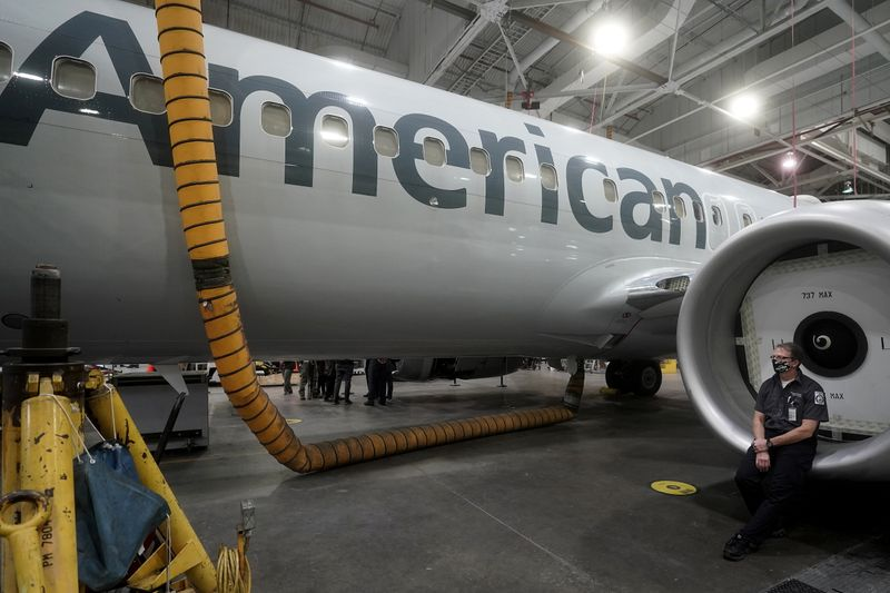 © Reuters. An American Airlines worker sits on an engine cowl of a Boeing 737 Max airplane in a maintenance hanger in Tulsa