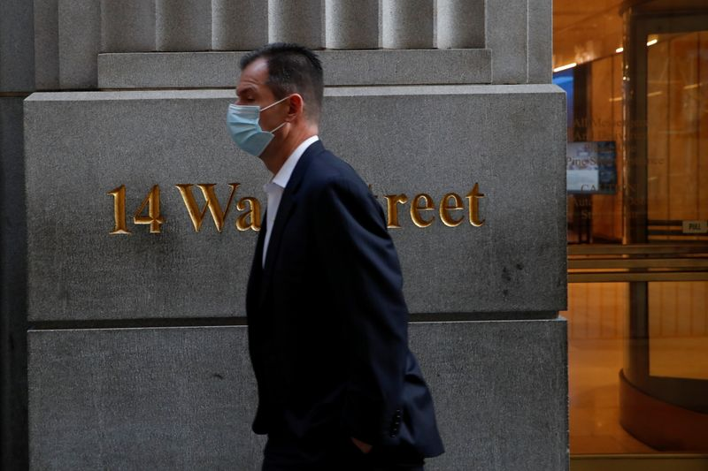 © Reuters. A man wearing a protective face mask walks by 14 Wall Street, as the global outbreak of the coronavirus disease (COVID-19) continues, in the financial district of New York